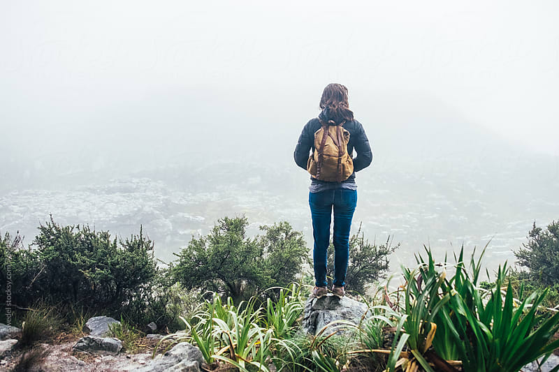 Female hiker with a backpack on a fog covered mountain by Micky Wiswedel for Stocksy United