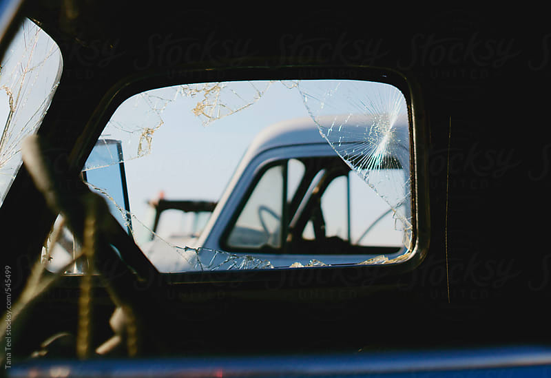Inside cab of abandoned vehicle looking out passenger window by Tana Teel for Stocksy United