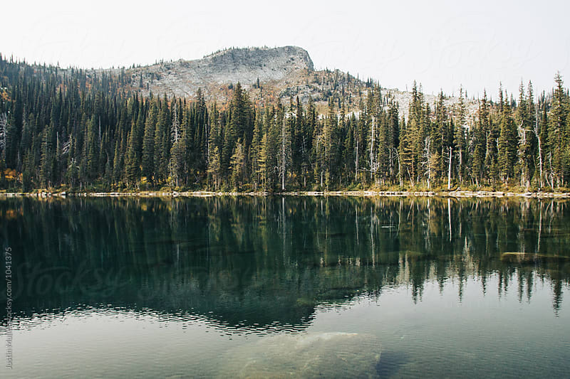 Alpine lake on a smoky afternoon.  by Justin Mullet for Stocksy United
