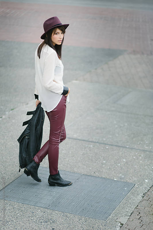A stylish brunette standing on the street looking  back by Ania Boniecka for Stocksy United