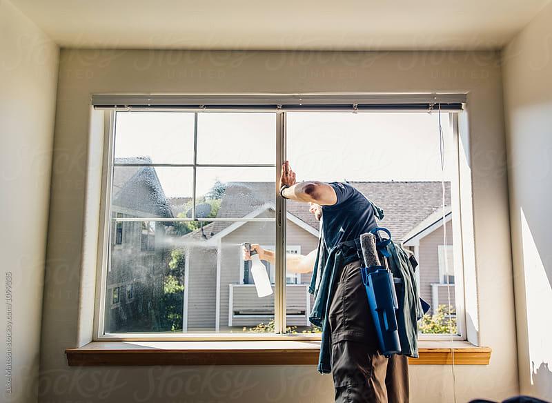 Window Washer Spraying Outside Of Condominium Window by Luke Mattson for Stocksy United