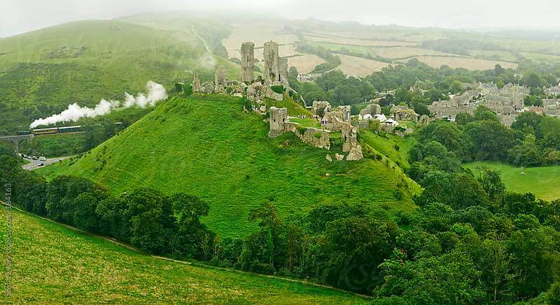 Medieval Corfe Castle among green hills of Dorset by Sasha Evory for Stocksy United