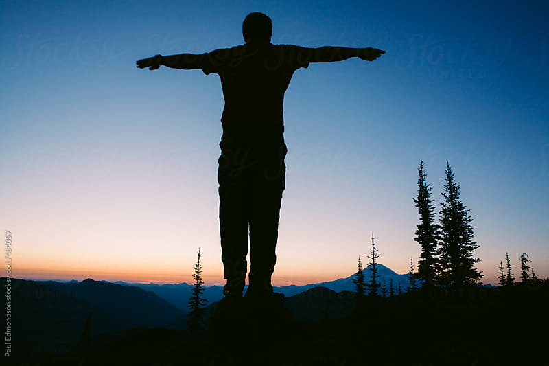 Silhouette of man standing with arms raised on mountain summit at dusk, Mt. Rainier in distance by Paul Edmondson for Stocksy United
