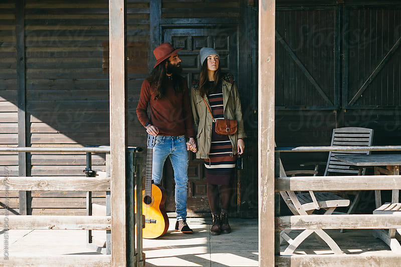 Hipster couple with a guitar holding hands on a cabin porch. by BONNINSTUDIO for Stocksy United