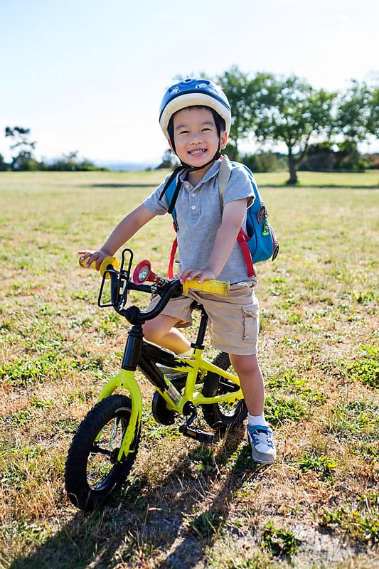 Happy Asian boy biking in the park by Suprijono Suharjoto for Stocksy United