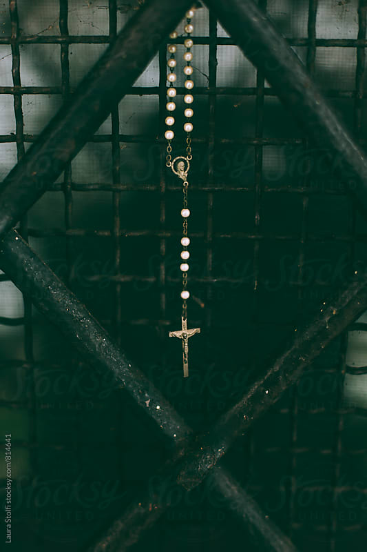 Close up of crucifix on rosary hanging from church's grate by Laura Stolfi for Stocksy United
