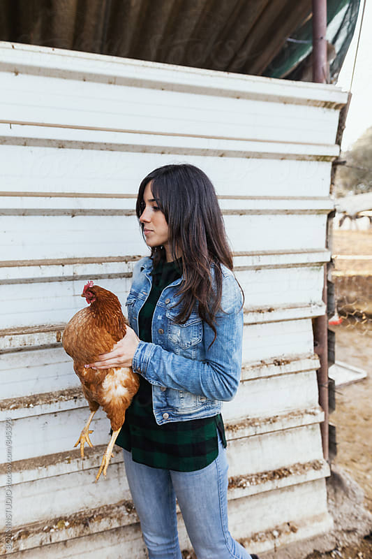 Side view of a woman holding a chicken on a farm. by BONNINSTUDIO for Stocksy United