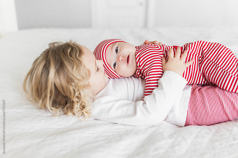 Big sister holding baby sister wearing striped Christmas pajamas by Amanda Worrall for Stocksy United