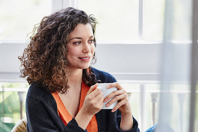 Woman With Coffee Cup Looking Away At Home by ALTO IMAGES for Stocksy United