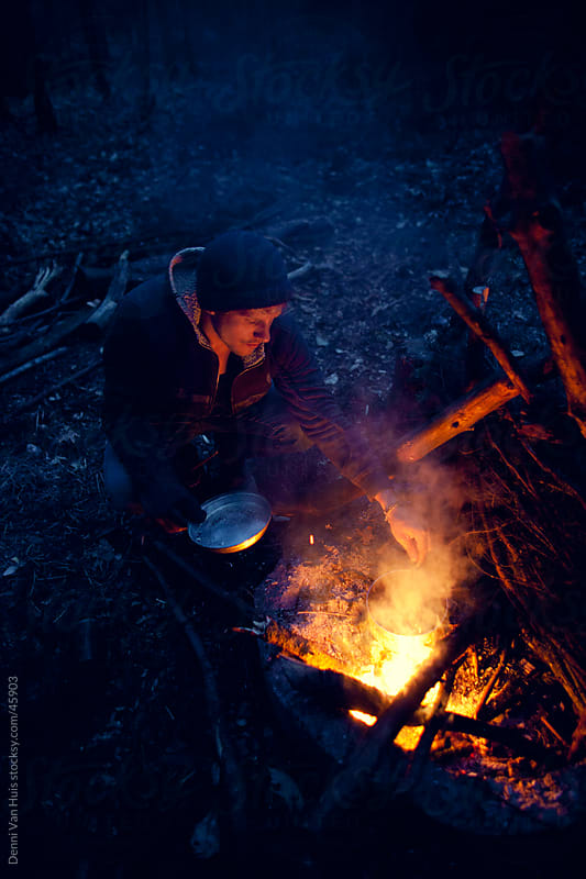 Young man sitting next to a campfire cooking dinner in a forest by Denni Van Huis for Stocksy United