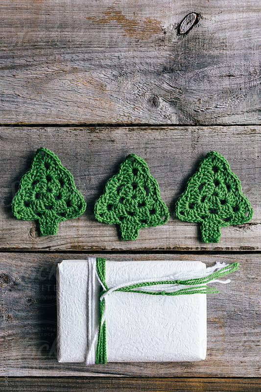 Simple Christmas gift tied with wool, with three crocheted Christmas Trees, vertical by Jacqui Miller for Stocksy United