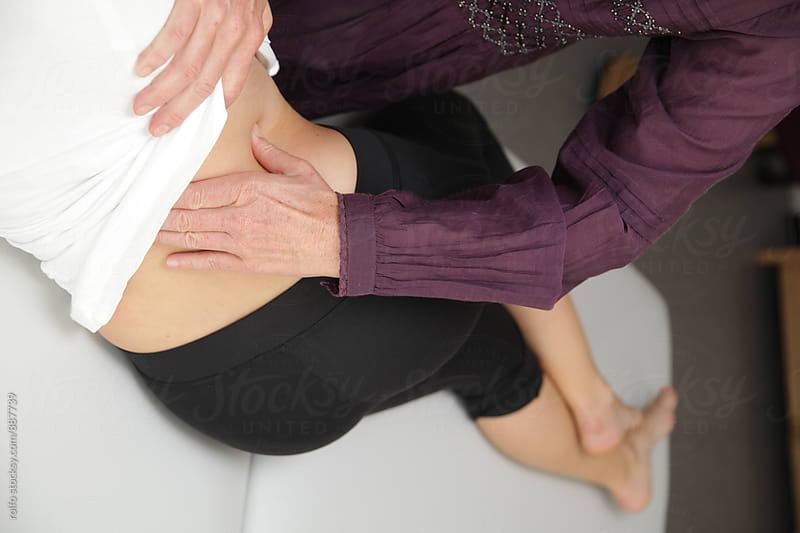 Body therapist massaging woman's back by rolfo for Stocksy United