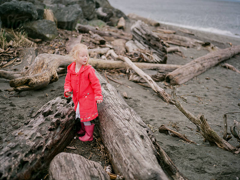Little girl stands amongs driftwood alone on the beach by Amanda Voelker for Stocksy United