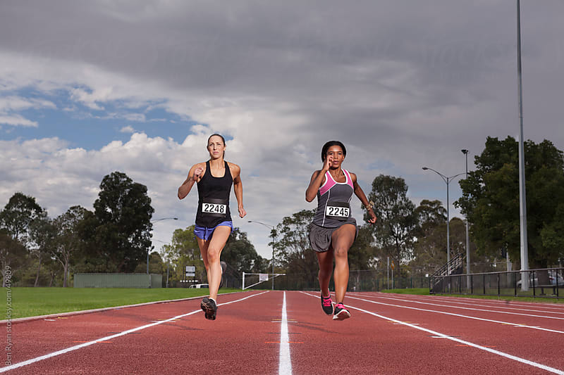 Caucasian and African female runners racing on an athletics track by Ben Ryan for Stocksy United