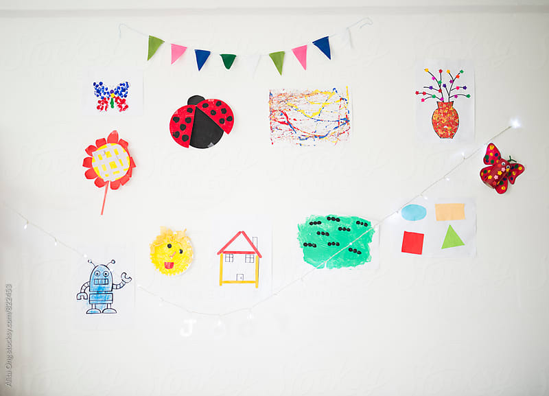 Child's artworks on the wall by Alita Ong for Stocksy United