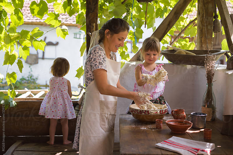 Mother and daughter making bread in summer kitchen by RG&B Images for Stocksy United