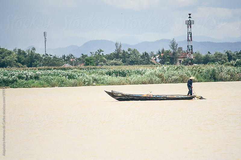 Asian fisherman on a boat on a river. Hoi An, Vietnam by Alejandro Moreno de Carlos for Stocksy United