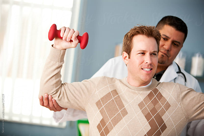 Exam Room: Man Uses Weights in Physical Therapy by Sean Locke for Stocksy United