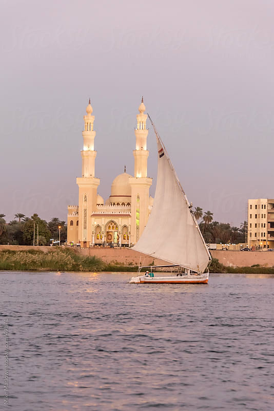 A boat sailing down the Nile past a mosque in Egypt. by Mike Marlowe for Stocksy United