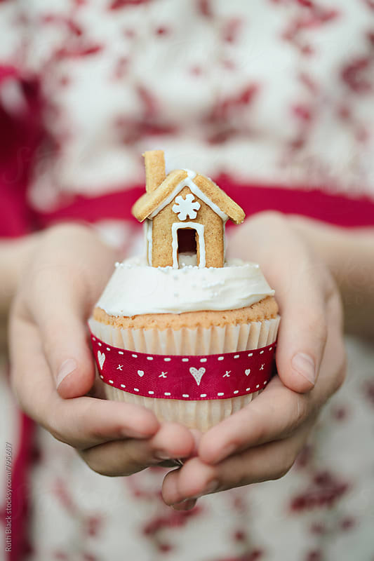 Hands holding gingerbread house cupcake by Ruth Black for Stocksy United