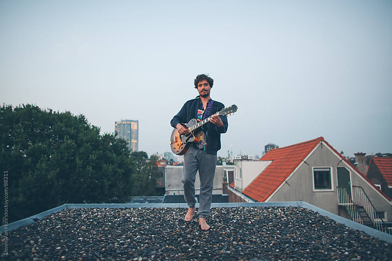 Creative musician playing guitar outside on a rooftop of a building  by Denni Van Huis for Stocksy United