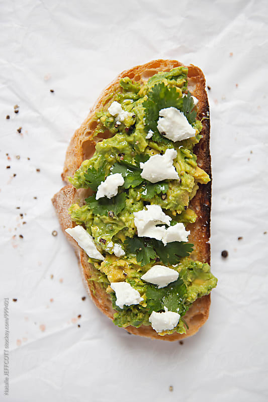 Close up of smashed avocado on toast with feta - goats cheese  for breakfast by Natalie JEFFCOTT for Stocksy United