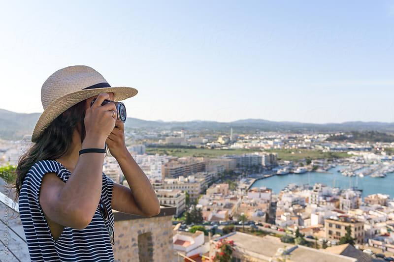 Young woman taking photos at mediterranean city by ACALU Studio for Stocksy United