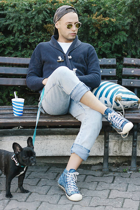 Portrait of a young male model siting on the bench with french bulldog  by Branislava Živić for Stocksy United