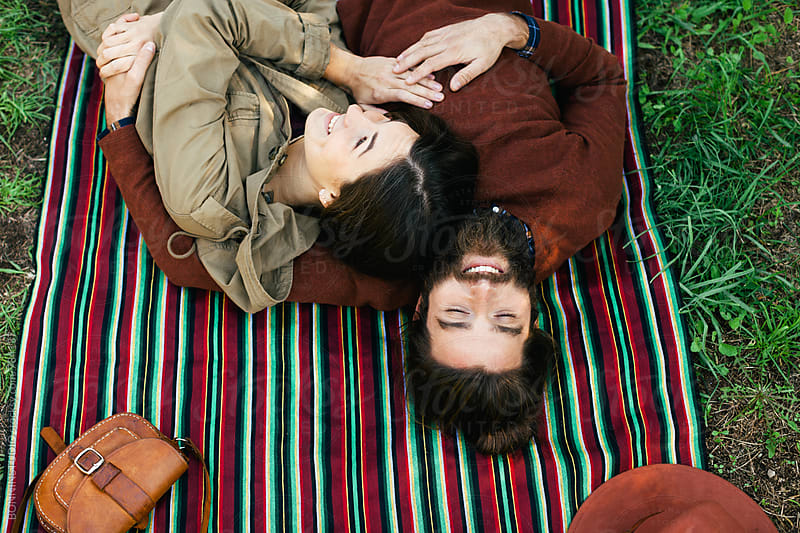 Overhead of couple embracing together resting on a striped blanket. by BONNINSTUDIO for Stocksy United