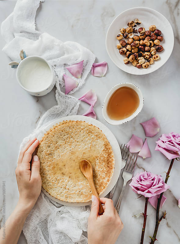 Making crepes with honey and hazelnuts by Tatjana Ristanic for Stocksy United