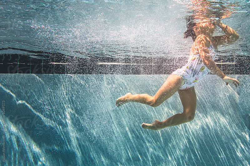 A Girl Holds Her Nose Underwater by Alison Winterroth for Stocksy United