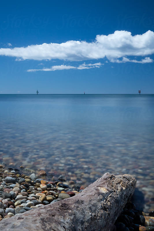 Stick on pebble beach under a cloudy blue sky by Gary Radler Photography for Stocksy United