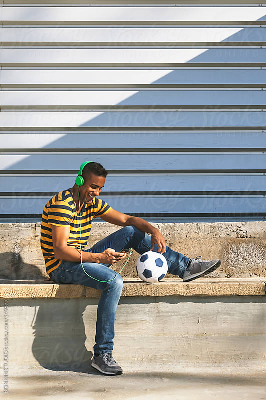 Black man sitting with soccer ball on cityscape.  by BONNINSTUDIO for Stocksy United