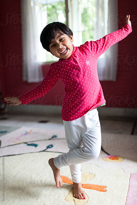 Little girl balancing on one leg by Saptak Ganguly for Stocksy United