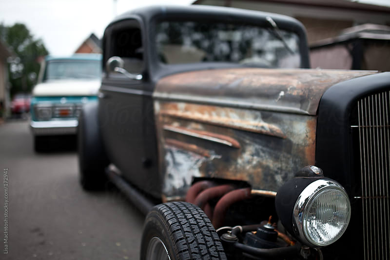 vintage, flat black hot rod with vintage blue and white truck behind by Lisa MacIntosh for Stocksy United