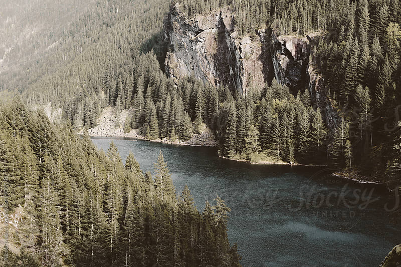 lake surrounded by trees and mountains by Nicole Mason for Stocksy United