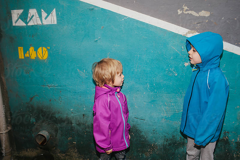Two kids in bright jackets facing each other and talking on a colourful urban street. by Julia Forsman for Stocksy United