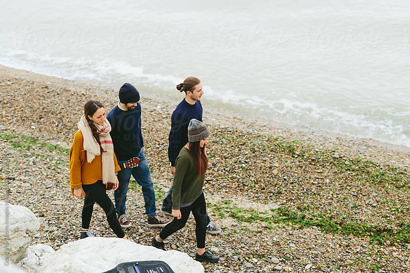 Group of friends walking on the beach by Good Vibrations Images for Stocksy United