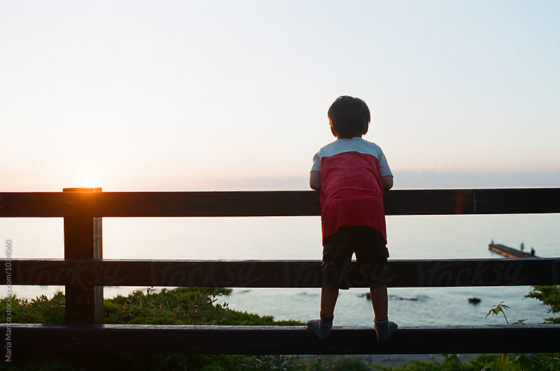 boy watches sunset over water by Maria Manco for Stocksy United
