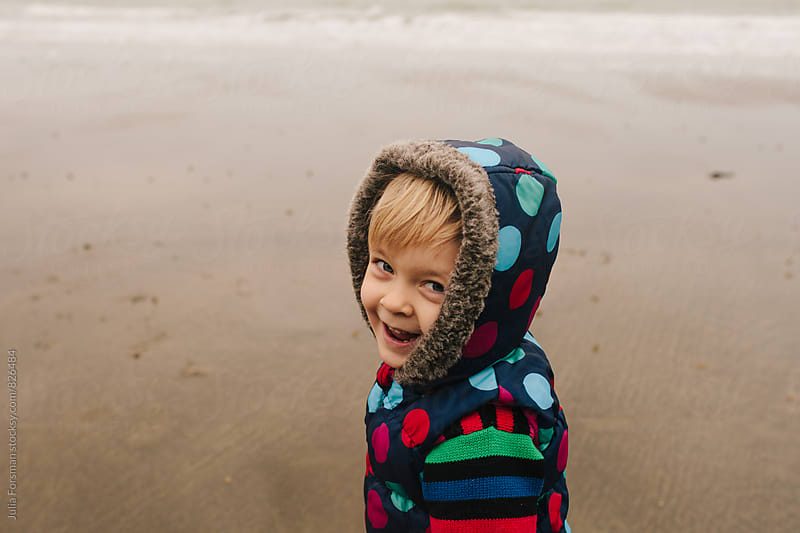 Close up of the cheeky face of a little girl as she runs on a beach. by Julia Forsman for Stocksy United