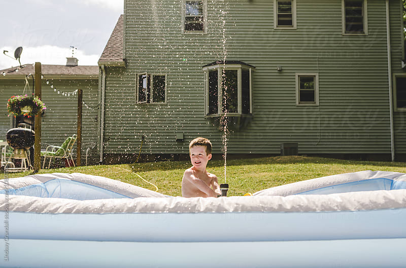 Child sitting in backyard pool spraying water from a hose by Lindsay Crandall for Stocksy United