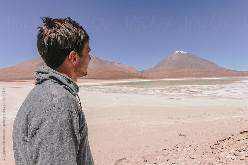 Young traveler man on desert landscape with mountains and lake, Bolivia by Alejandro Moreno de Carlos for Stocksy United