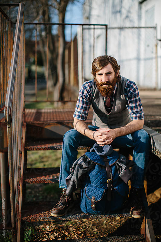A hipster with a backpack sitting in an urban setting by Jakob for Stocksy United