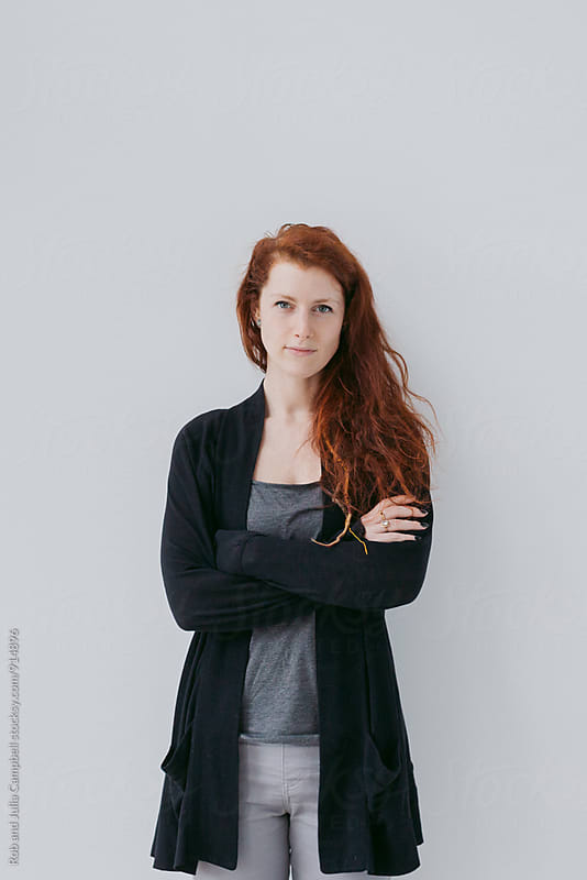Serious portrait of red head woman on simple white background by Rob and Julia Campbell for Stocksy United