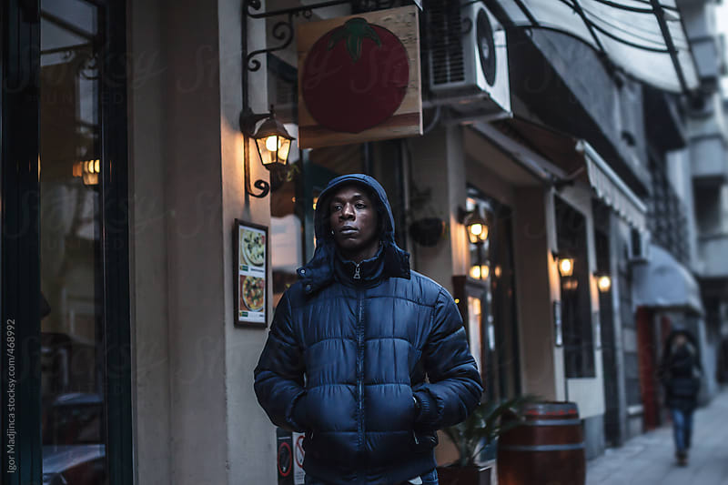 street portrait of black boy,Italian restaurant in the background by Igor Madjinca for Stocksy United