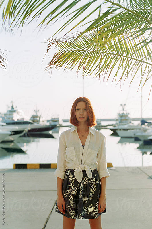 Woman standing at sea port by Lyuba Burakova for Stocksy United