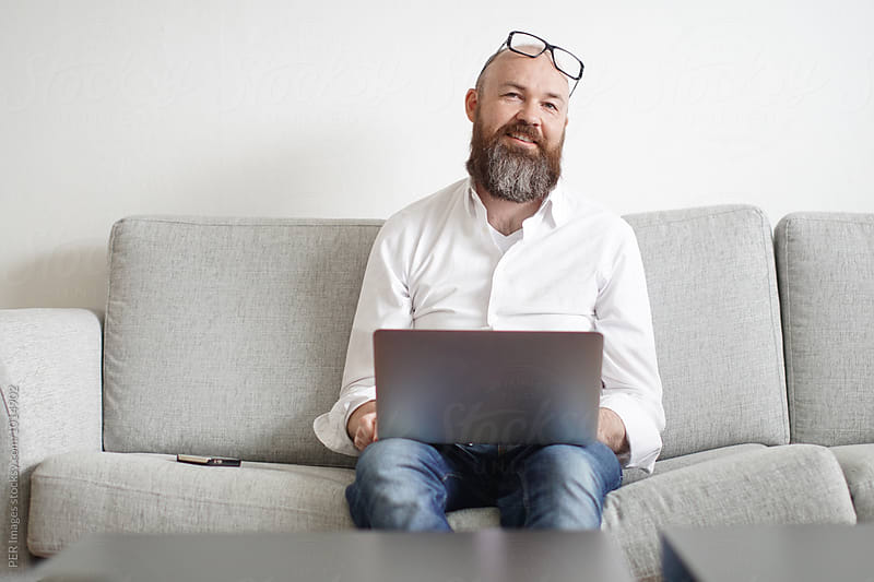 Happy stylish man with beard working from home by Per Swantesson for Stocksy United