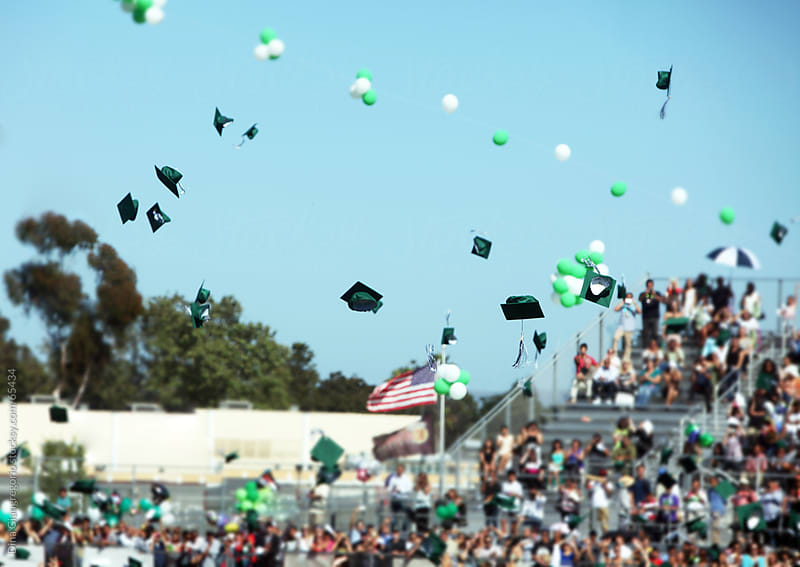 Graduation caps in mid air with crowd shown in background by Dina Giangregorio for Stocksy United