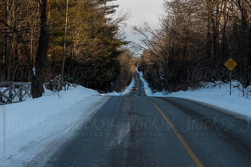 Car on Winter Road at Sunset  by Jeff Wasserman for Stocksy United