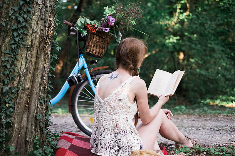 Young Woman Reading a Book in the Park by Mosuno for Stocksy United